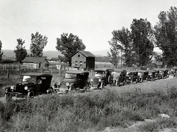 Historic photo of a line of old cars along a dirt road near a farm